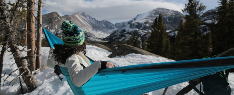 Woman sitting in hammock in the snow looking at a mountain range