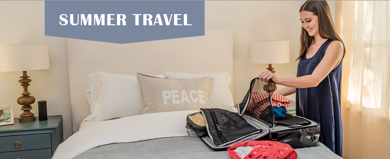 Woman packing a suitcase in a hotel room.