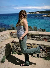 Casey in Corsica on a cliff overlooking a scenic view of the ocean.