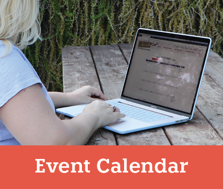 Woman looking at an events calendar on a laptop at a picnic table - View our events calendar