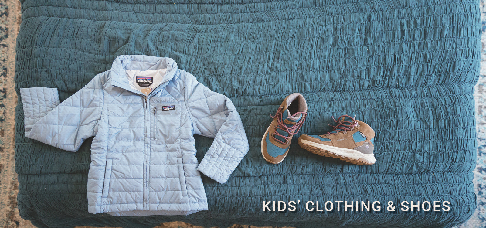 Kids Patagonia Radalie Jacket and Merrell Ontario 85s sitting on a bed