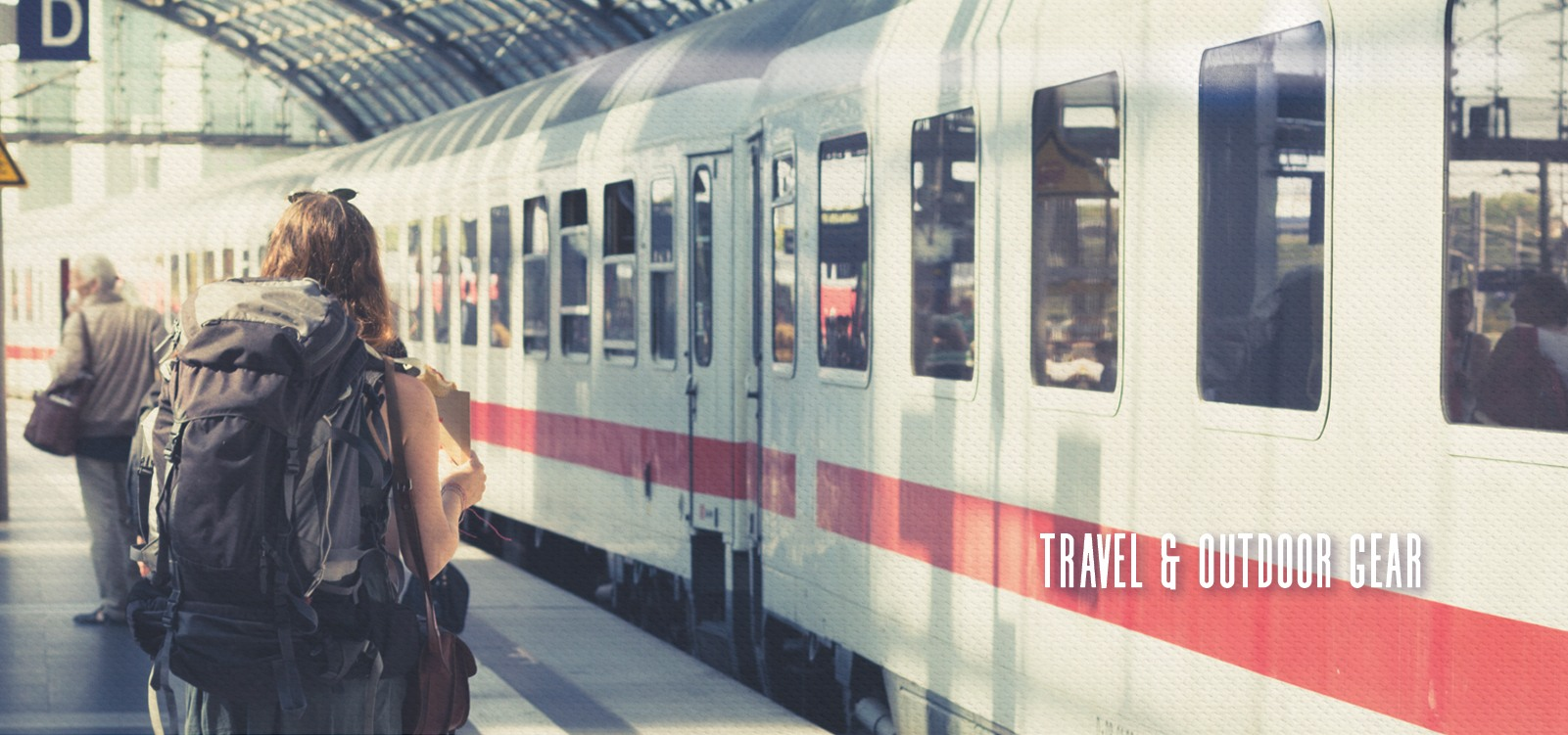 Girl standing by a train wearing a backpacking pack.