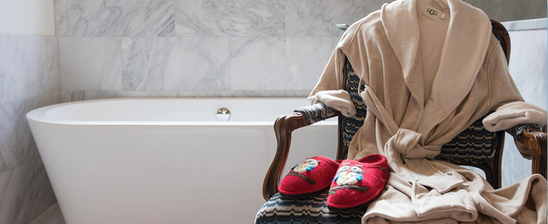 Ugg Robe and red Halflinger slippers on a chair in a bathroom