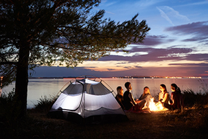 Family camping scene with a sunset, a tent, and people around a fire