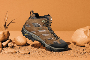 Mid Height Moab shoe on a orange, yellow background with rocks and plants