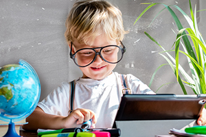 Kid with glasses working on a tablet with a globe, clock, soccer ball and plant