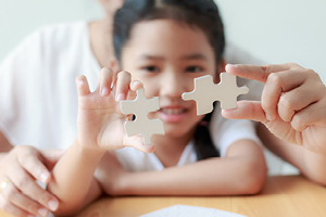 Girl holding a puzzle piece with a woman behind her holding another puzzle piece next to it